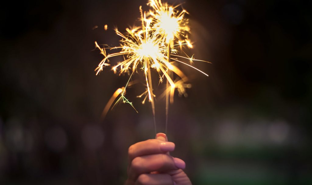 A woman's hand holding two Bonfire Night sparklers bursting with bright white flames